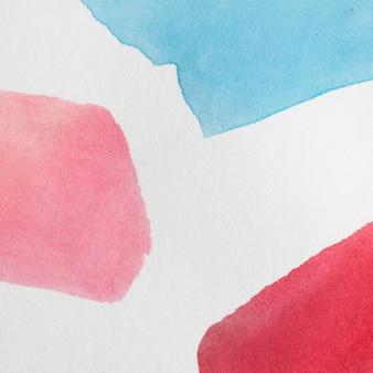 Variedad de manchas pintadas a mano sobre superficie blanca.