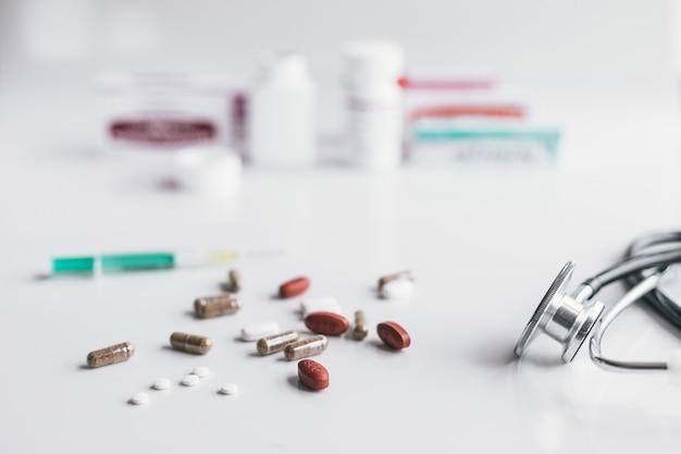 Variedad de medicamentos y drogas con un estetoscopio.