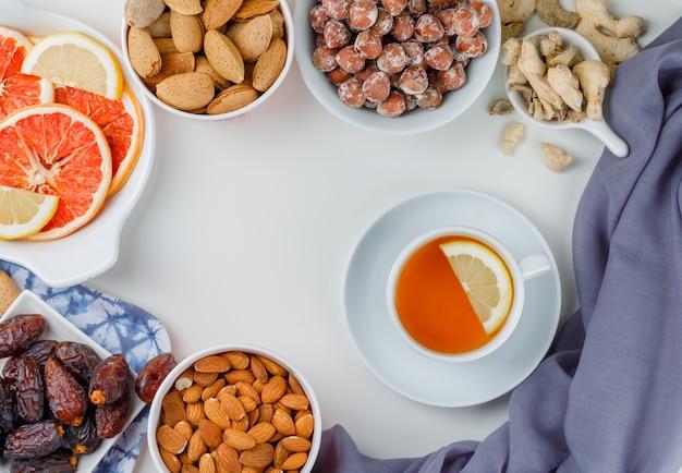 Variedad de nueces con una taza de té, dátiles, rodajas de cítricos y jengibre en platos blancos.