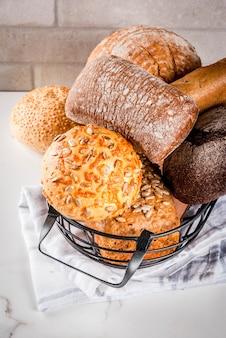 Variedad de pan de grano casero fresco en una canasta de metal fondo de mármol blanco