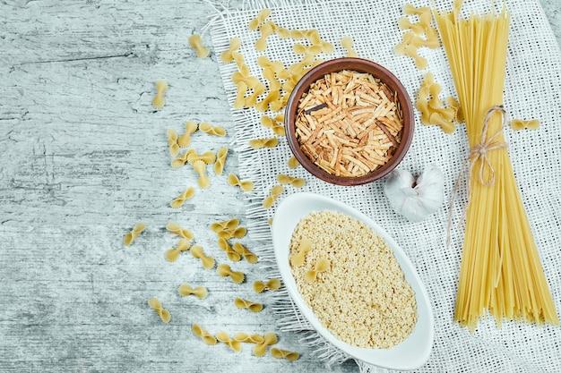 Variedad de pasta cruda con ajo y mantel blanco.