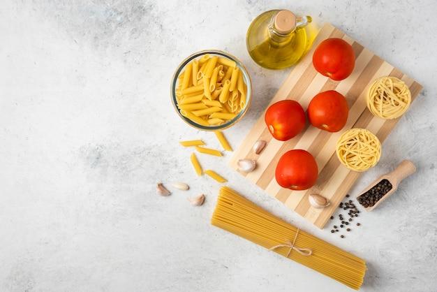 Variedad de pasta cruda, botella de aceite de oliva, granos de pimienta y tomates sobre fondo blanco.