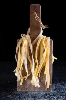 Una variedad de pasta italiana casera cruda sin cocer tagliatelle en una tabla de cortar