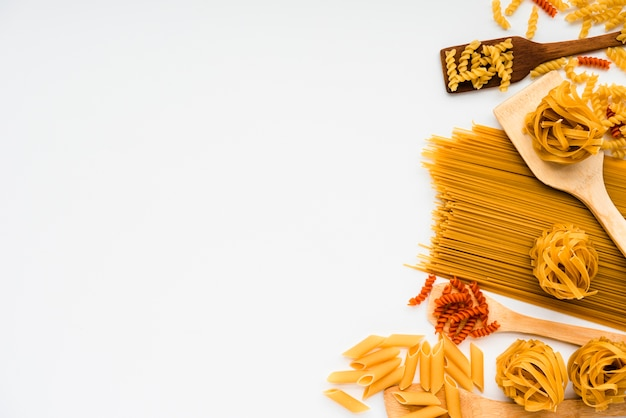 Variedad de pasta italiana cruda y espátula de madera sobre fondo blanco.