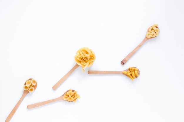Variedad de pastas italianas crudas del trigo integral en la cuchara de madera aislada sobre el contexto blanco