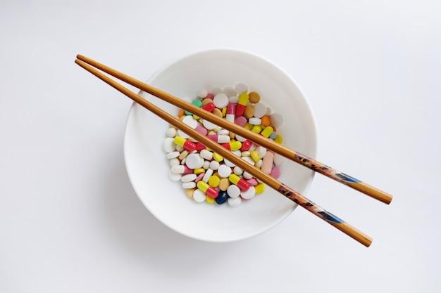 Variedad de pastillas en un plato con palos chinos aislados en blanco