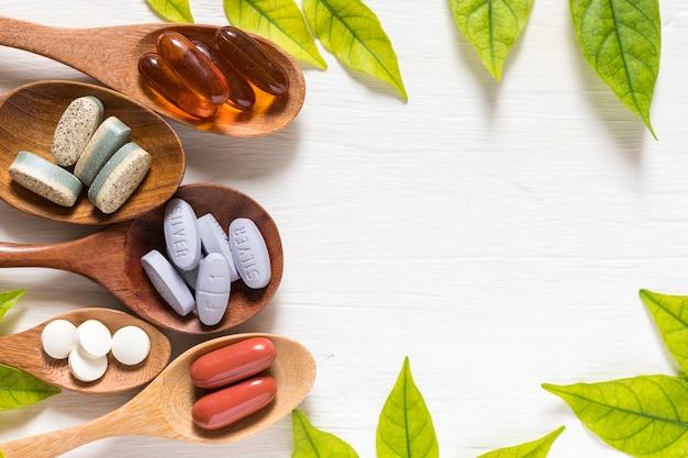 Variedad de píldoras de vitaminas en cuchara de madera sobre fondo blanco con hoja verde, plano lay sur
