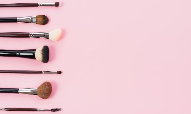 Variedad de pinceles de maquillaje diferentes sobre fondo rosa