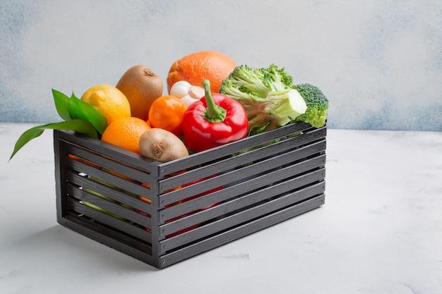 Variedad de productos, verduras y frutas para mantener la inmunidad en una caja negra sobre un fondo blanco.