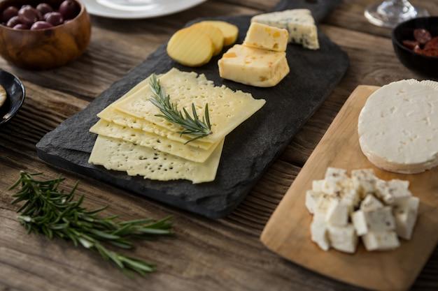 Variedad de queso, aceitunas, galletas y hierbas de romero en mesa de madera.