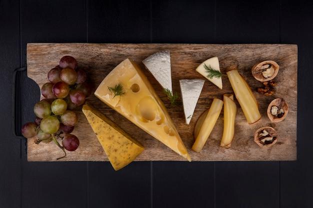 Variedad de queso de vista superior en un soporte con uvas y nueces
