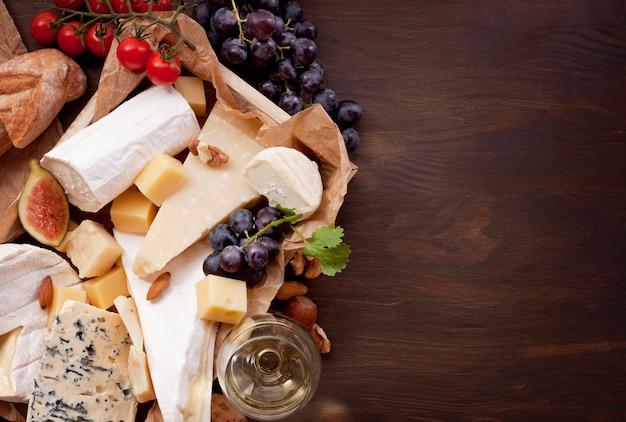 Variedad de quesos diferentes con vino, frutas y frutos secos.