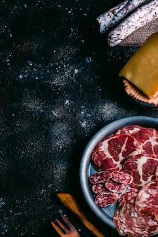 Variedad de quesos y embutidos típicos de españa en mesa de madera vintage. queso de oveja, fuet, chorizo, chorizo. comida española. espacio libre para texto. vista superior.