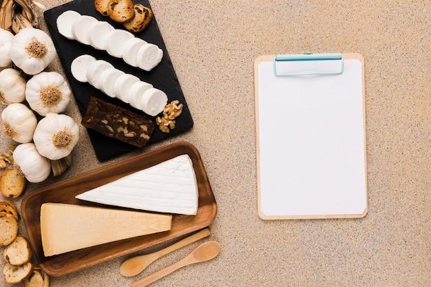 Variedad de quesos con ingredientes orgánicos cerca de papel negro en el portapapeles sobre azulejo