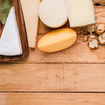 Variedad de quesos; pan y nueces en mesa con espacio para texto.