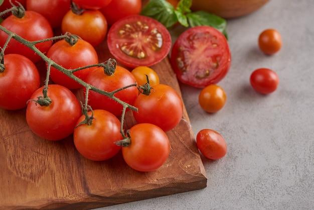 Variedad roja fresca de tomates con especias de albahaca, pimienta. concepto vegetal de tomate. comida de dieta vegana. cosecha de tomates.