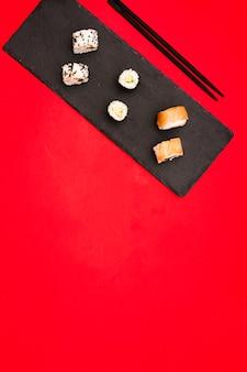 Variedad de rollos de sushi calientes dispuestos en piedra de pizarra con palillos sobre fondo de color con espacio para texto
