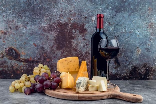 Variedad de sabrosos quesos y uvas con vino.