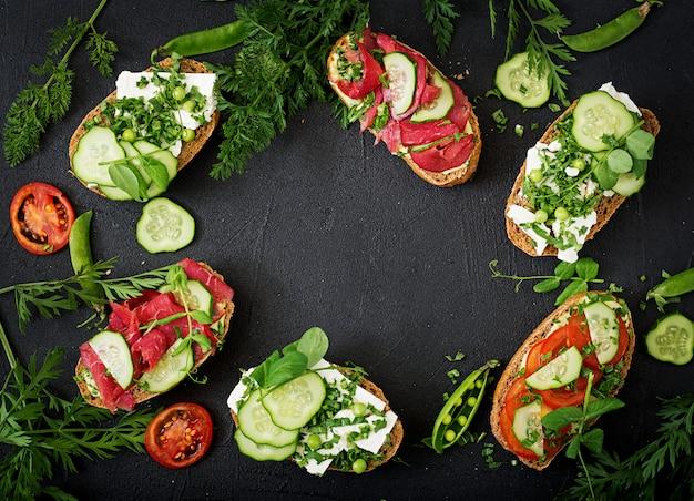 Variedad de sándwiches saludables en una mesa oscura en un estilo rústico. . lay flat