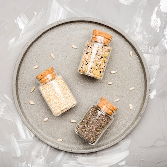 Variedad de semillas trituradas en pequeños frascos de vidrio vista superior
