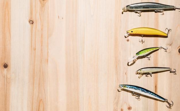 Variedad de señuelos de pesca de colores en el escritorio de madera