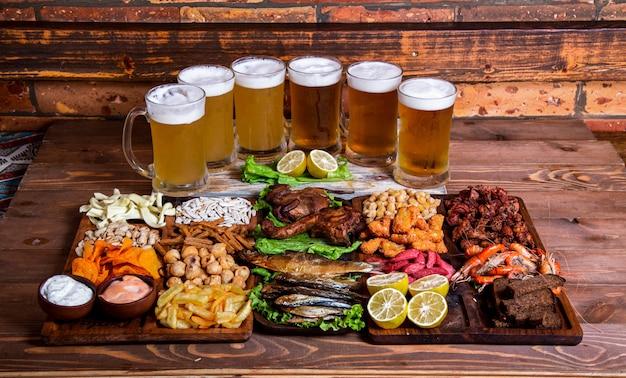 Variedad de snacks y frutos secos con vasos de cerveza.