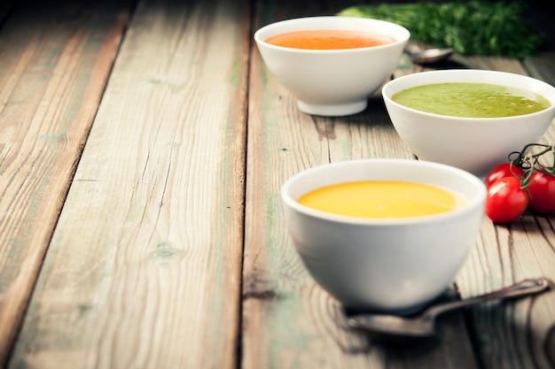 Variedad de sopas de crema sobre la mesa de madera vieja.