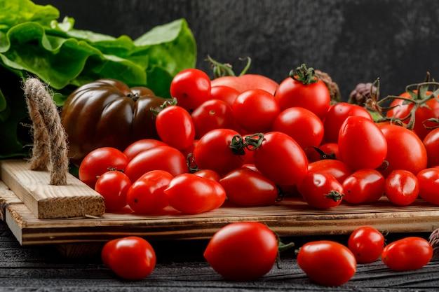 Variedad de tomates en una bandeja hecha a mano con vista lateral de lechuga en madera y pared oscura
