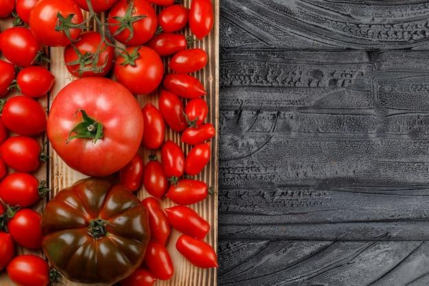 La variedad de tomates en una bandeja de madera plana yacía en una pared gris