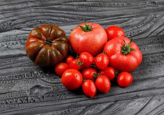 Variedad de tomates en una pared de madera gris. vista de ángulo alto.