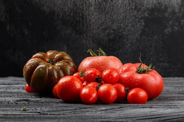 Variedad de tomates en la pared de madera y oscura, vista lateral.
