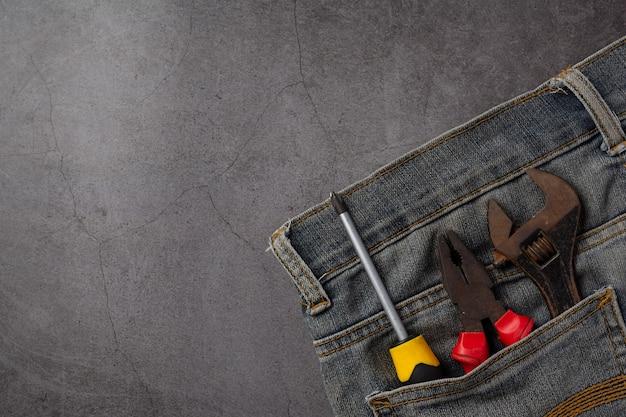 Variedad de útiles herramientas y jeans sobre fondo oscuro