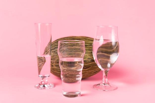 Variedad de vasos de agua y melón.