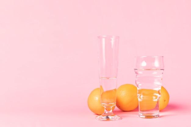 Variedad de vasos llenos de agua y naranjas.