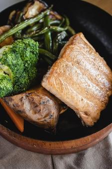 Variedad de verduras asadas con salmón.