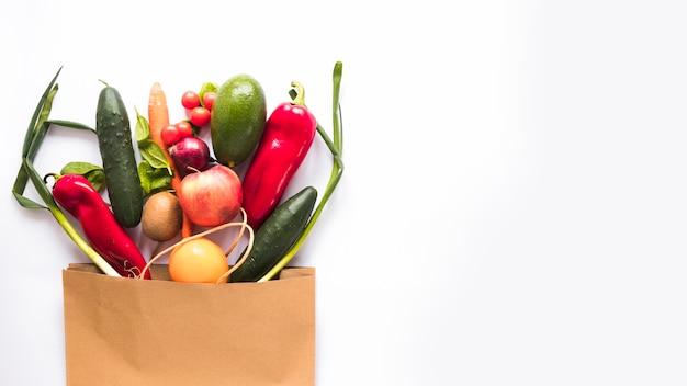 Variedad de verduras en bolsa de papel sobre fondo blanco