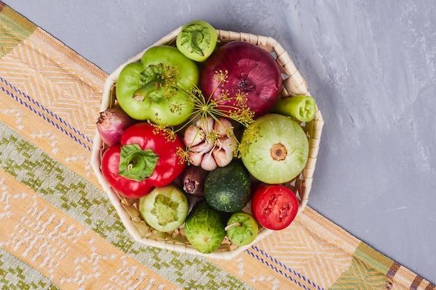 Variedad de verduras en una canasta de bambú, vista superior.