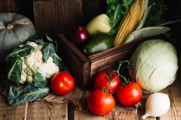 Variedad de verduras y una canasta de madera.