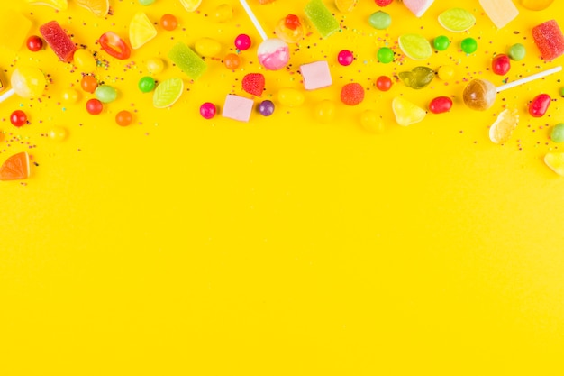 Variedades de dulces dulces coloridos en superficie amarilla.