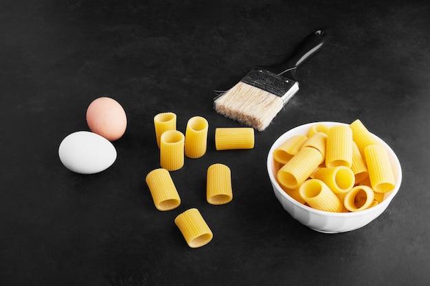 Variedades de pasta cruda en tazas de cerámica con huevos alrededor.
