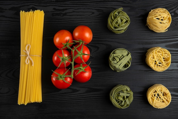 Variedades de pasta italiana con tomates en la mesa negra