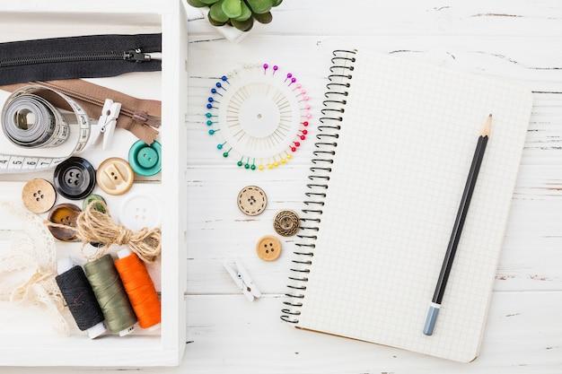 Varios accesorios de costura con bloc de notas y lápiz sobre fondo de madera