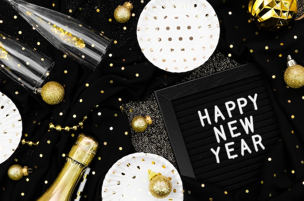 Varios accesorios y gafas sobre fondo negro y tarjeta de feliz año nuevo
