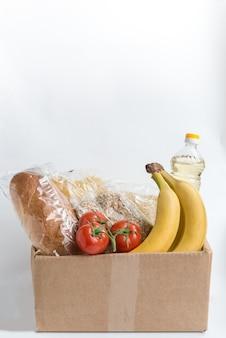 Varios alimentos en la caja de cartón con espacio de copia