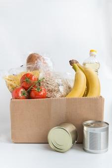 Varios alimentos enlatados en la caja de cartón sobre una mesa
