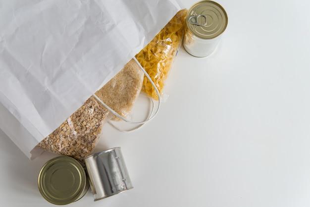 Varios alimentos enlatados, pasta, arroz y cereales crudos en una mesa en una bolsa de papel con espacio de copia