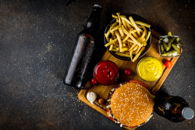 Varios alimentos para fiestas, hamburguesas, papas fritas, papas fritas, pepinos en vinagre, cebollas, tomates y botellas de cerveza fría