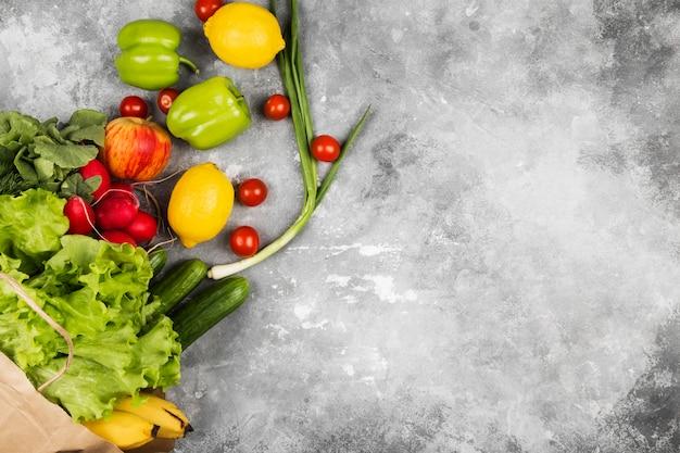 Varios alimentos saludables en bolsa de papel en el espacio gris. vista superior, copia espacio. espacio de comida