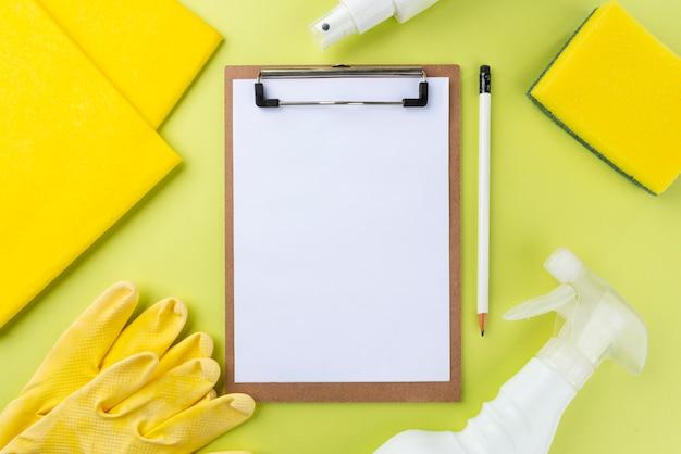 Varios artículos de limpieza en la pared verde y el bloc de notas en blanco. concepto de productos de limpieza.
