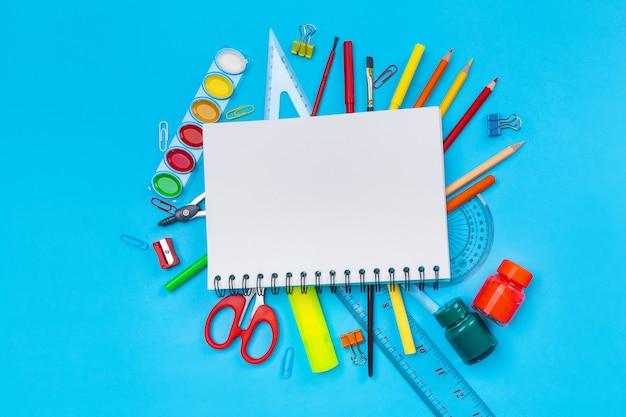 Varios artículos de papelería en forma de lápices, rotuladores, bolígrafos, tijeras, clips de papel, botellas de pintura